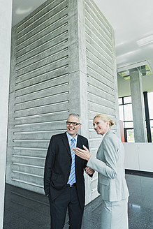 Germany, Stuttgart, Business people in office lobby, smiling - MFPF000229