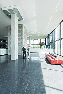 Germany, Stuttgart, Business people having discussion at office lobby - MFPF000232