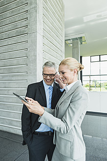 Germany, Stuttgart, Businesswoman with digital tablet while man talking on phone - MFPF000235