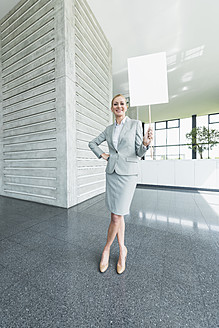 Germany, Stuttgart, Businesswoman standing with blank signs in office lobby, smiling, portrait - MFPF000238