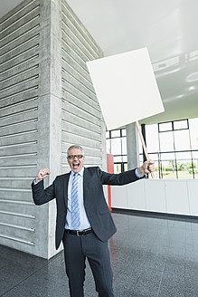 Germany, Stuttgart, Businessman holding placard in office lobby - MFPF000241