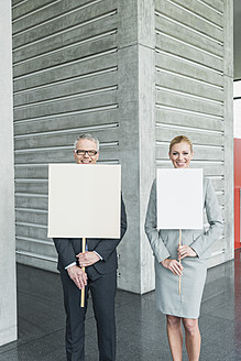 Germany, Stuttgart, Business people holding blank signs in office lobby, smiling, portrait - MFPF000244