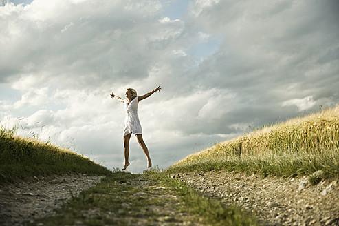 Germany, Bavaria, Mature woman jumping in grain field - RNF000966
