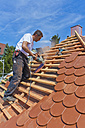 Germany, Baden-Wuerttemberg, Stuttgart, Mid adult man cutting roof tile - WDF001254