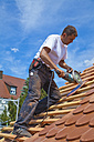 Germany, Baden-Wuerttemberg, Stuttgart, Mid adult man cutting roof tile - WDF001264
