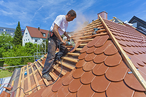 Germany, Baden-Wuerttemberg, Stuttgart, Mid adult man cutting roof tile - WDF001271