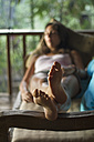 Indonesia, Young woman relaxing in veranda - MBEF000423