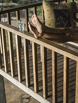 Indonesia, Young woman relaxing in veranda - MBEF000436