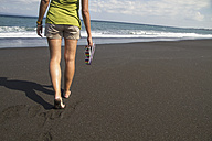 Indonesia. Young woman walking on black sand - MBEF000445