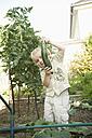 Germany, Bavaria, Boy holding cucumber in garden - RNF000998