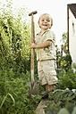 Germany, Bavaria, Boy holding shovel in garden - RNF001001