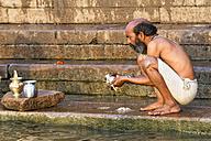 India, Uttar Pradesh, Banaras, Senior man washing pots at River Ganges - FO004187