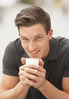 Germany, Young man with coffee cup, smiling, portrait - WBF001463