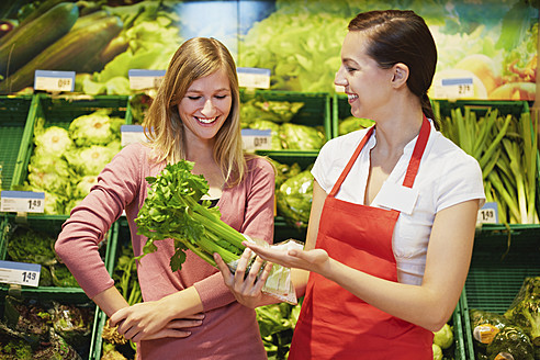 Germany, Cologne, Young womens with celery in supermarket - RKNF000005