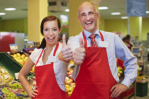 Germany, Cologne, Man and woman in supermarket showing thumbs up, smiling, portrait - RKNF000017
