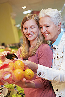 Germany, Cologne, Womens with smart phone and oranges in supermarket - RKNF000020