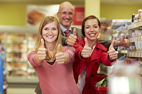 Germany, Cologne, Man and women showing thumbs up in supermarket - RKNF000035