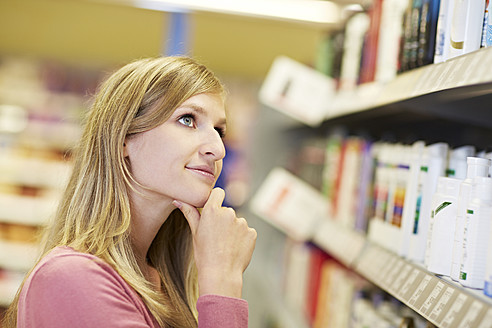 Germany, Cologne, Young woman thinking in supermarket - RKNF000044