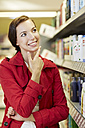 Germany, Cologne, Young woman thinking in supermarket - RKNF000047