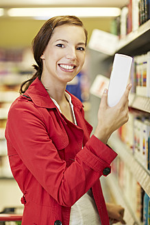 Germany, Cologne, Young woman in supermarket, smiling, portrait - RKNF000049