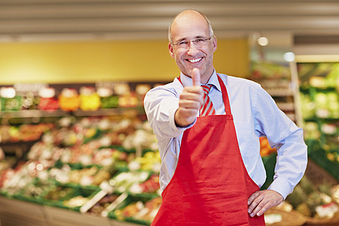 Germany, Cologne, Mature man showing thumbs up in supermarket - RKNF000073