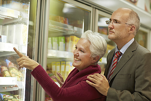 Germany, Cologne, Mature couple choosing from freezer in supermarket - RKNF000081