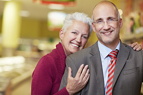 Germany, Cologne, Mature couple in supermarket, smiling, portrait - RKNF000090