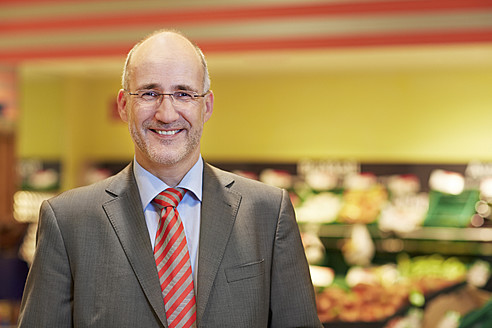 Germany, Cologne, Mature man in supermarket, smiling, portrait - RKNF000093