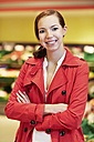 Germany, Cologne, Young woman in supermarket, smiling, portrait - RKNF000096