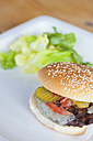 USA, Texas, Cooked bacon cheese burger with lettuce in plate - ABAF000226