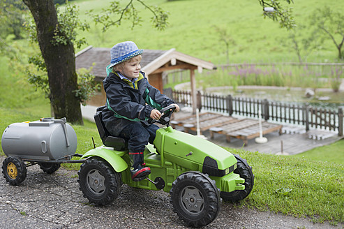 Germany, Bavaria, Boy sitting in toy tractor with trailer - MJF000085