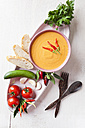 Bowl of gazpacho with bread, tomatoes and chillies on tray - ECF000094