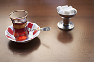 Turkey, Close up of turkish tea in glass with sugar cube on table - FLF000136