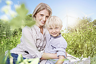Germany, Cologne, Mother and son sitting on blanket at picnic - PDYF000012