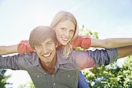 Germany, Cologne, Young couple flying, smiling, portrait - PDYF000033