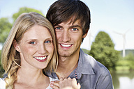 Germany, Cologne, Young couple smiling, portrait - PDYF000054