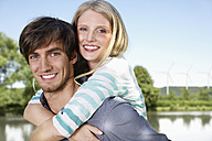 Germany, Cologne, Young couple embracing, smiling, portrait - PDYF000063
