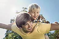 Germany, Cologne, Father and son flying, smiling - PDYF000105