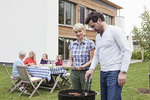 Germany, Bavaria, Nuremberg, Couple grilling barbecue, family sitting in background - RBYF000153