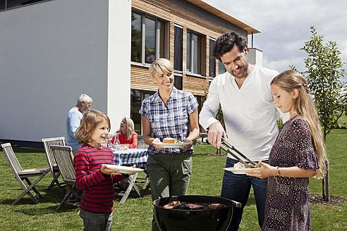 Germany, Bavaria, Nuremberg, Family barbucue in garden - RBYF000126
