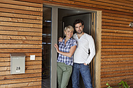 Germany, Bavaria, Nuremberg, Mature couple standing at front door of house - RBYF000201