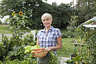 Germany, Bavaria, Nuremberg, Mature woman with vegetables in garden - RBYF000204