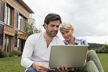Germany, Bavaria, Nuremberg, Mature couple using laptop in garden - RBYF000210