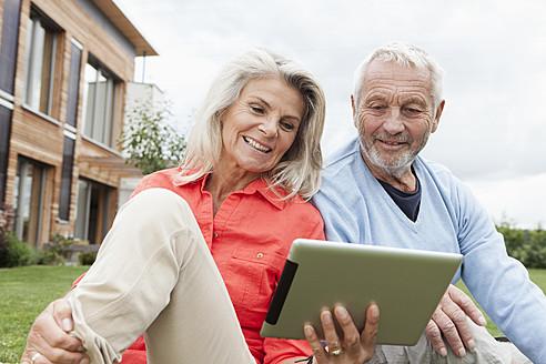 Germany, Bavaria, Nuremberg, Senior couple using digital tablet in garden - RBYF000214