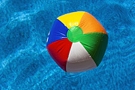 Austria, Linz, Colourful beach ball floating in swimming pool - EJWF000070