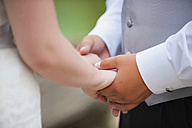USA, Texas, Bride and groom holding hands, close up - ABAF000228