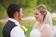 USA, Texas, Bride and groom looking at each other, smiling - ABAF000255