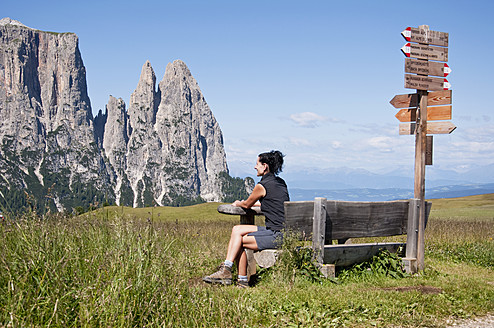 Italy, Mid adult woman sitting on bench and looks to Schlern  at South Tyrol - UMF000442