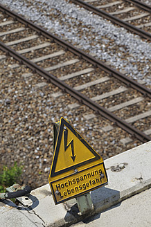 Germany, Bavaria, High voltage sign on railway track - AXF000245