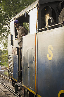 India, Tamil Nadu, Man looking out of Nilgiri Mountain Railway connecting Mettupalayam and Ooty - MBE000549